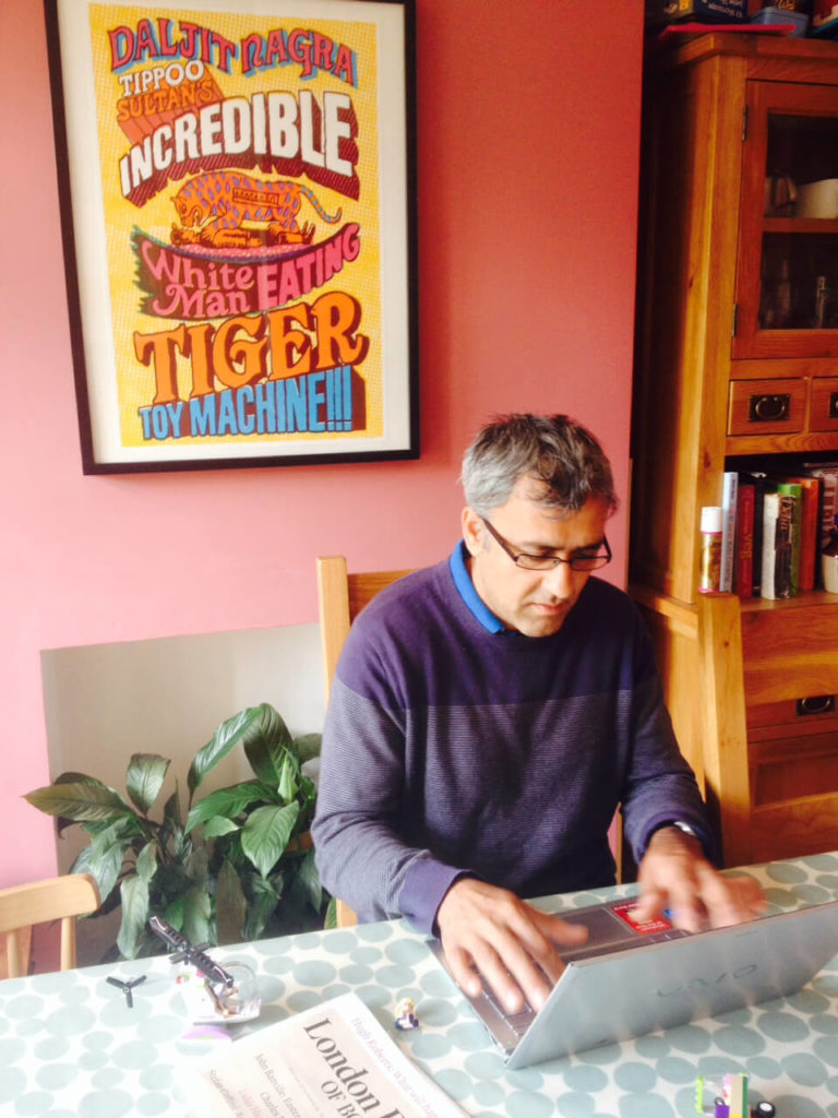 Image shows Poet Dajit Nagra at work at his desk
