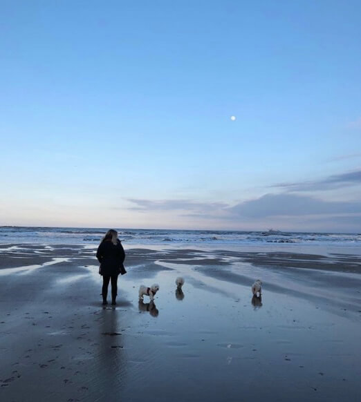 Chloe Hall from Bumble and Bloom Media on the beach with her three dogs